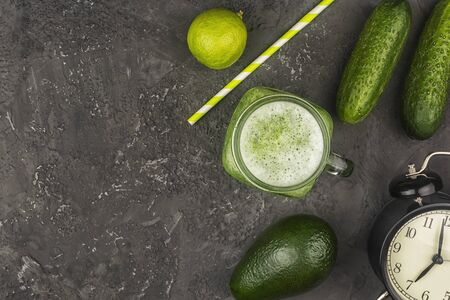 On a black  a jar with a cucumber smoothie.
