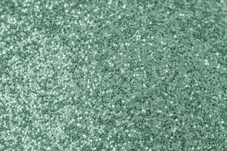 Bright shiny turquoise background for sites and layouts. The surface of many small sparkles, closeup. Selective focus. 版權商用圖片