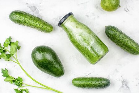 On a light background a bottle with cucumber smoothie, avocado and parsley. The concept of the use of cucumber juice. Photo above.