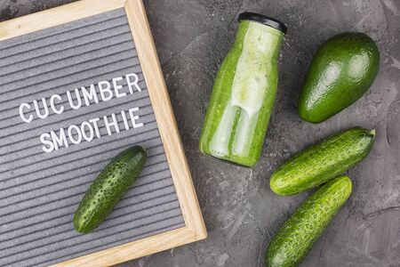 On a dark background a bottle with cucumber smoothie, avocado and felt board. The concept of the use of cucumber juice. Photo above.
