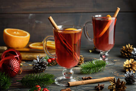 Cozy Christmas photo with two glasses of mulled wine, orange and cinnamon. Holiday atmosphere. 免版税图像