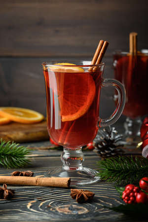 Glass with Christmas mulled wine, orange and cinnamon. Holiday atmosphere. Close-up photo.