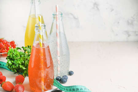 Three bottles of drinks with basil seeds. On a gray background, copy space. Healthy juices.
