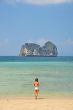 A sexy bikini girl on white sand beach with crystal clear sea, Thailand photo