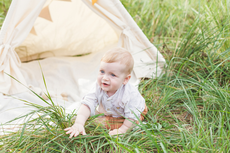 One year cute boy in a teepee outdoors. Stock Photo