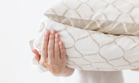 Hands of woman holding modern beige bed linen pile, white wall background in trend, minimalism clean home concept