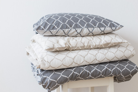 Two bedding sets in grey and beige, cool for two children, for siblings. Modern bed linen, in trend, minimalism clean home concept