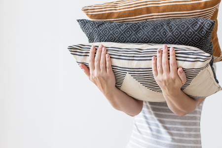 Hands of woman holding modern three pillows for sofa, white wall background in trend, minimalism clean cozy home concept. Autumn decor for home living room