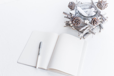 Open blank notebook, pen and handmade decoration candlestick with pine cones and branches in white tones. Festive Christmas and New Year concept