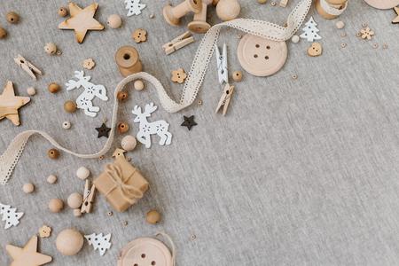 Rzemiosło i drewniane Boże Narodzenie flatlay na tle tkaniny. Materiały drewniane, bawełniane koronki i bożonarodzeniowe symbole. Miejsce na tekst
