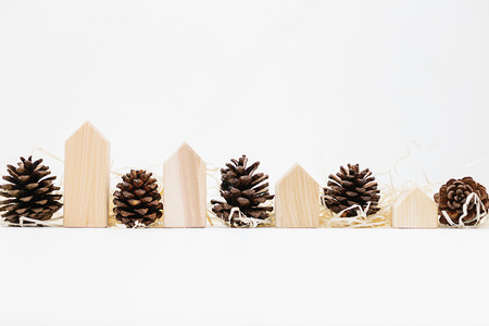 Lined up set of pinecones on wood shavings and wooden blocks house shape. Real estate sale, drop in prices and market stagnation concept, copy space. Holiday time