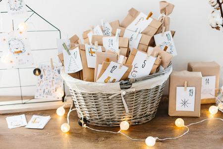 Calendario de Adviento esperando Navidad. Cesta con sobres con números y tareas para niños de pie sobre armario
