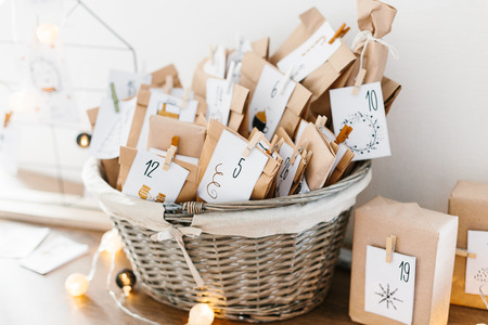 Advent calendar waiting for Christmas. Basket with envelopes with numbers and tasks for children standing on cabinet
