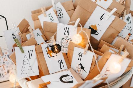 Calendario dell'avvento in attesa del Natale. Cestino con buste con numeri e compiti per bambini in piedi su mobile