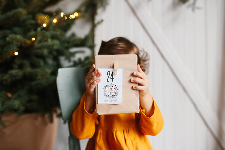 Cute curly toddler girl wearing mustard linen dress showing gift box advent calendar with 24 number in studio near christmas tree. Minimalistic stylish scandinavian christamas decoration.