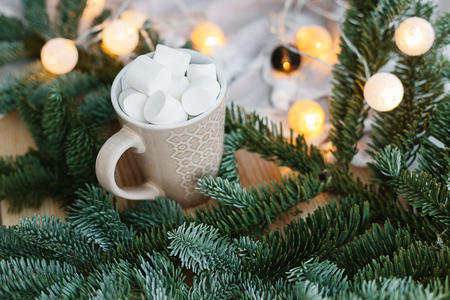 Spruce branches in basket and cup with cacao and marshmallow. Rustic new year christmas decoration at home, scandinavian interior