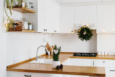 Piccolo albero di Natale in vaso di fiori bianco cucina moderna bianca in stile scandinavo decorato per lo sfondo di Natale. Cipresso, Chamaecyparis lawoniana Ellwoodii