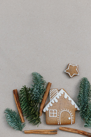 Christmas composition homemade gingerbread cookies. Gingerbread house shape in the fir branches forrest. Building concept 스톡 콘텐츠