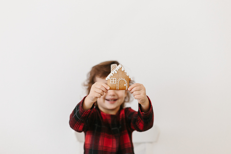 Little girl holding homemade gingerbread cookies house shape. Christmas time. Real estate concept