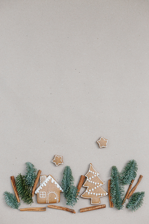 Christmas composition homemade gingerbread cookies. Gingerbread house shape in the fir branches forrest. Building concept Stock Photo