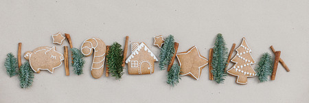 Christmas homemade gingerbread cookies in the line on craft paper background. Christmas bakery banner 免版税图像