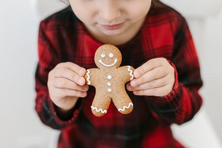 Little girl holding homemade ginger man cookies. Christmas time