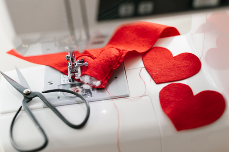 Hnadmade felt red heart sewing machine scissors. Valentines day concept.