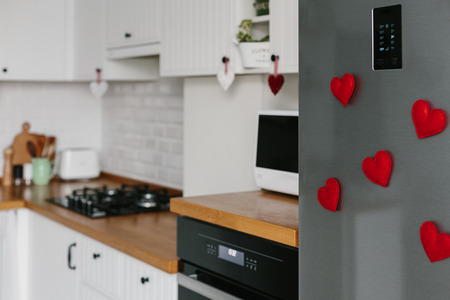Handmade red felt heart shape magnets on refrigerator door. White kitchen on background. Diy valentines day decoration for home. Place for text