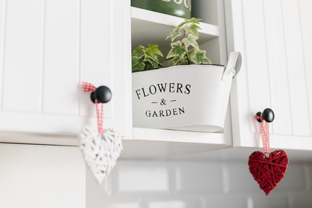 Heart shape decoration hanging on white kitchen cabinets close up kitchen details. Decorate your kitchen with love