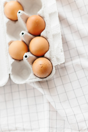Eggs in egg tray on white kitchen towel. Selective focus 스톡 콘텐츠