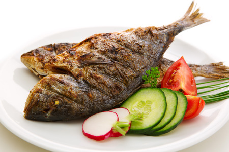 dorada: Close-ups of two dorada fish with vegetables  and onion isolated on white. Fried fish.