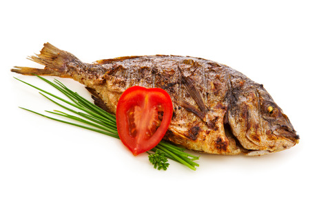 fish isolated: Close-ups of dorada fish with vegetables  and onion isolated on white. Fried fish.