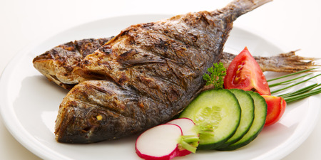 dorada: Closeups of two dorada fish with vegetables and onion isolated on white Stock Photo
