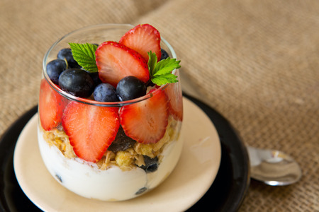 fruit plate: Fresh Yogurt with strawberries and blueberries isolated on brown cloth background.