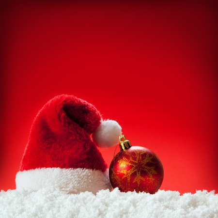 hatred: Christmas  red background with Santa hat.Red Santa hat and christmas ball.