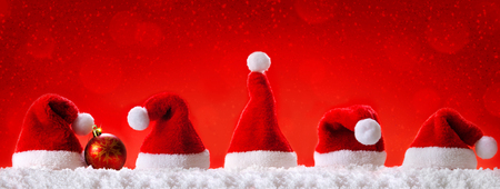 red: Seven red santa hats isolated on red background.Christmas  red background with Christmas hats.Red  Christmas hats. Stock Photo