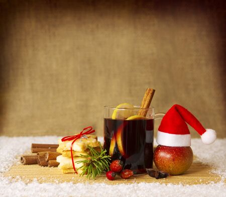 drinking tea: Glass with mulled wine on a snow  background and santa hat. Stock Photo