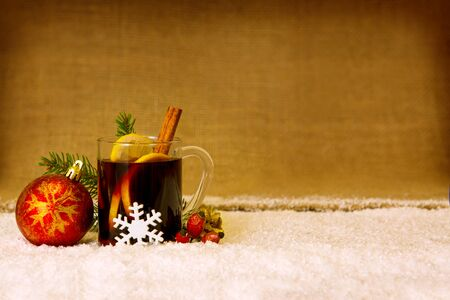 cookies: Glass with mulled wine on a snow  background .Christmas mulled wine and red ball. Stock Photo