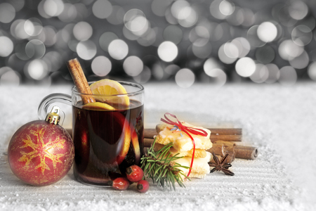 punch spice: Glass with mulled wine on a snow  background.Grey  bokeh background.