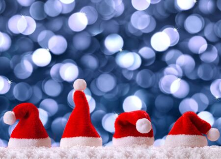 christmas hats: Four red santa hats isolated on blue bokeh background.Christmas background with Christmas hats.Red Christmas hats.