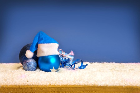 blue flame: Christmas decoration and snow background.Blue christmas balls and santa hat  isolated .
