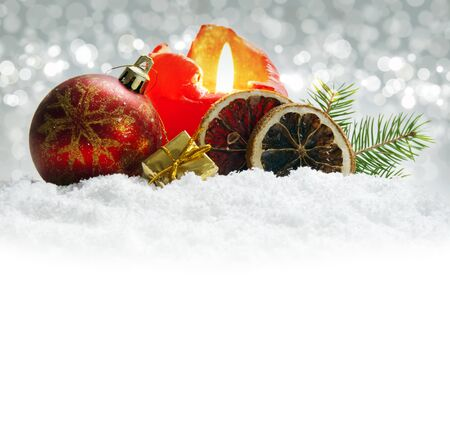 flamme: Cristmas ball and red Advent candle.Silver background an snow. Stock Photo
