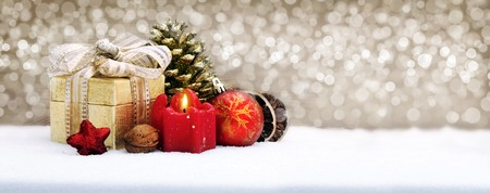 flamme: Christmas gift box with decoration.Christmas gift box with  decorations and red candle.Golden background an snow.
