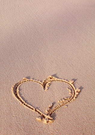 evoke: Heart drawn on sand. Heart in sand at the summer beach.