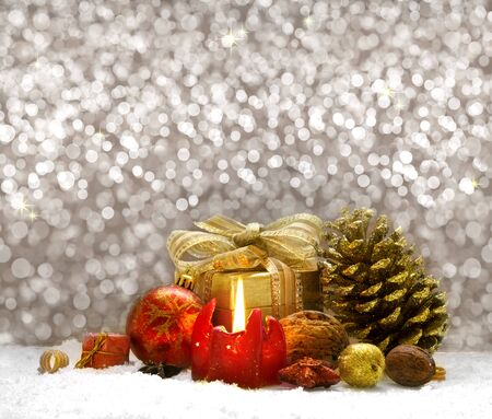 flamme: Christmas gift box with decoration isolated on bokeh background.Christmas gift box with  decorations and red candle.Golden bokeh background and white snow.