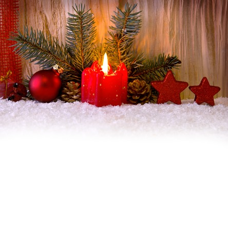 'christmas ball': Composition with Burning candle, fir tree and Christmas decorations isolated on wooden background.Wchite snow and red Christmas decoration.
