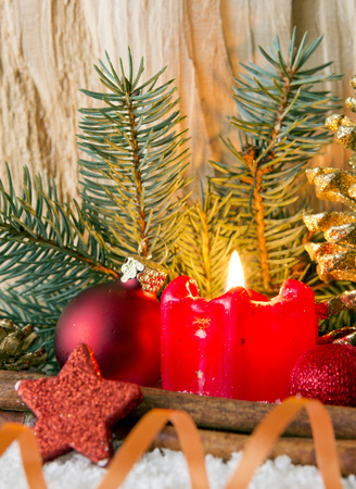 flamme: Burning candle, fir tree and Christmas decorations isolated on wooden background.Wchite snow and red Christmas decoration. Stock Photo