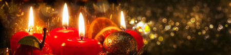 advent wreath: Velas del advenimiento con la decoraci�n de Navidad a la luz atmosf�rica. Cuatro velas de Adviento rojas.