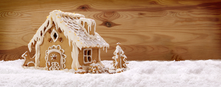 Gingerbread house on wooden background.Christmas background.White snow. Stock Photo