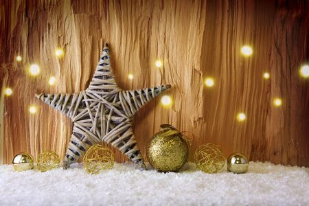 Christmas card with gold Christmas balls, winter snow and star on wooden background. Christmas banner with place for your text